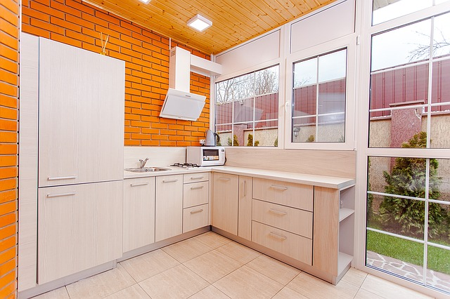 světlá kuchyně, oranžové obložení, okno ven